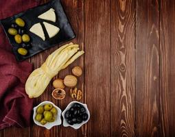 Top view of cheese, nuts, and olives photo