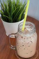 Iced coffee with a green plant photo