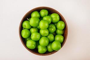 Top view of sour plums in a wooden bowl on a white background
