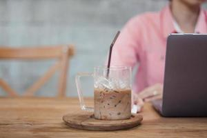 Woman working on a laptop in a coffee shop with an iced coffee