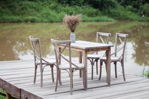 mesa y sillas de madera en un muelle exterior