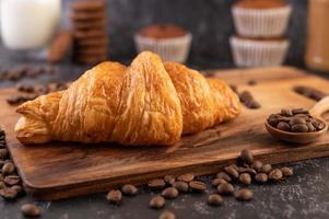 Croissant sobre una tabla de madera con granos de café.