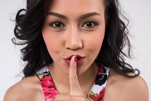 Young girl making silence gesture photo
