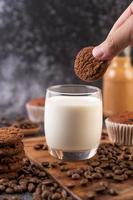 Hand dipping a cookie in milk