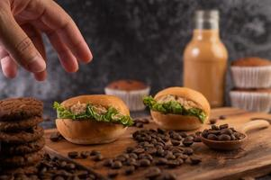 Burgers on a cutting board, including cupcakes and coffee beans