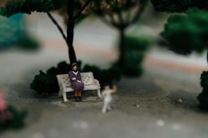 Close-up of miniature people sitting in chairs in the park