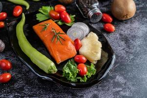 Raw salmon fillet with pepper, kiwi, pineapples, and rosemary photo