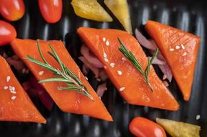 Raw salmon fillet with pepper, kiwi, pineapples, and rosemary