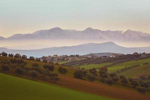 Panorama of the Italian countryside with misty and snowy mountai