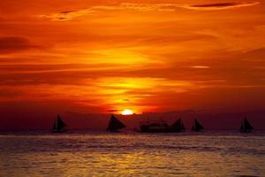 Sunset on beach with sailing boats photo