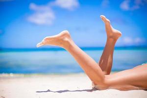 Female tanned slim legs on the white sandy tropical beach