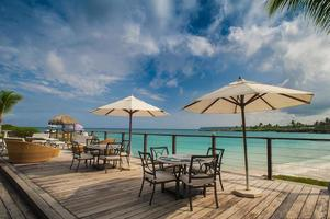 Outdoor restaurant at the seashore. Table setting in tropical Summer