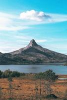 Mountain near a body of water under a blue sky
