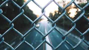 Grey chain-link fence and a road