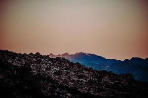 Black rocky mountain under orange sky