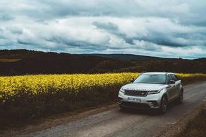 Mallorca, Spain, 2020 - Silver Range Rover on a road a field of yellow flowers