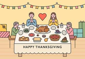 Families are sitting around a table on Thanksgiving and praying