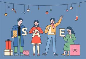 People are standing holding the SALE alphabet.