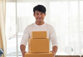 joven sonriente repartidor logístico sosteniendo cajas