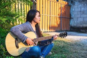 Woman sitting outside playing a guitar photo
