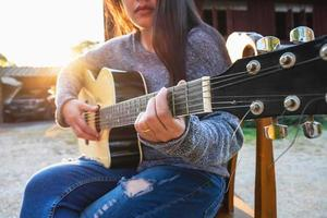 Woman playing a guitar outside photo