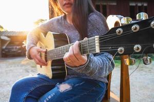 mujer tocando una guitarra afuera