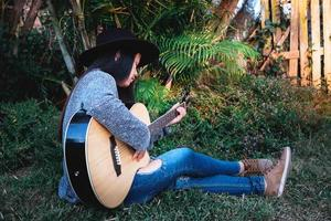 Woman sitting in the grass playing guitar photo
