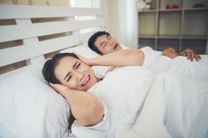 Sleeping woman blocking ears with man snoring in bed photo