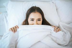 Woman waking up in her bed, lazy in the morning