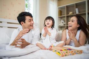 niño feliz con padres jugando en casa foto