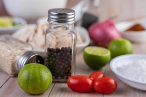 Close-up of limes and tomatoes with pepper on a wooden table
