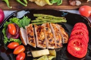 Chicken steak with salad vegetables on a black plate photo