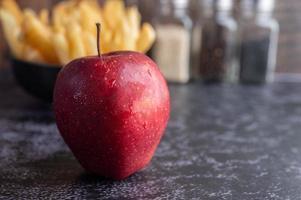 manzanas rojas con papas fritas en el fondo foto