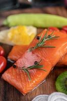 Raw salmon fillets with pepper, kiwi, pineapple and rosemary