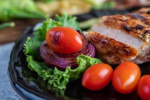 Filete de pollo con ensalada de verduras en una placa negra
