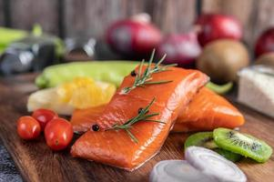 Raw salmon fillets with pepper, kiwi, pineapple and rosemary photo