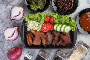 Fried pork topped with chilies and vegetables photo
