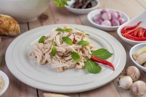 Ensalada de pollo en un plato blanco con hojas de menta