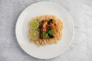 fideos y conservas de pescado en un plato blanco foto
