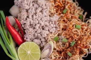 carne de cerdo picada en una sartén con limón, chiles y albóndigas foto