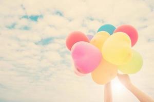 manos sosteniendo globos de colores bajo el sol del verano