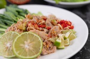 Ensalada picante de cerdo con lima y verduras y acompañamientos foto