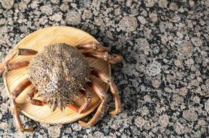 Top view of a crab on a wooden plate