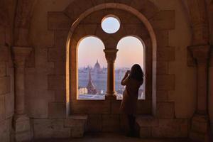 mujer de pie en una ventana en budapest foto