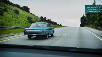 Vintage blue car driving on the California freeway