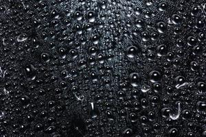 Droplets on transparent plastic sheet, black background