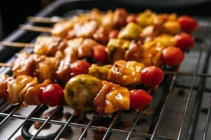 BBQ grill with a variety of meats, tomato and peppers