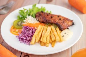 Fish steak with french fries, fruit and vegetables