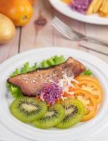 Filete de pescado con patatas fritas, frutas y verduras.