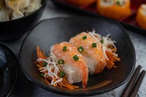 sushi plateado con salsa y palillos